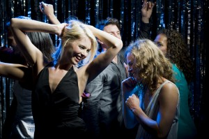 Young people dancing at a nightclub, under blue coloured spotlights