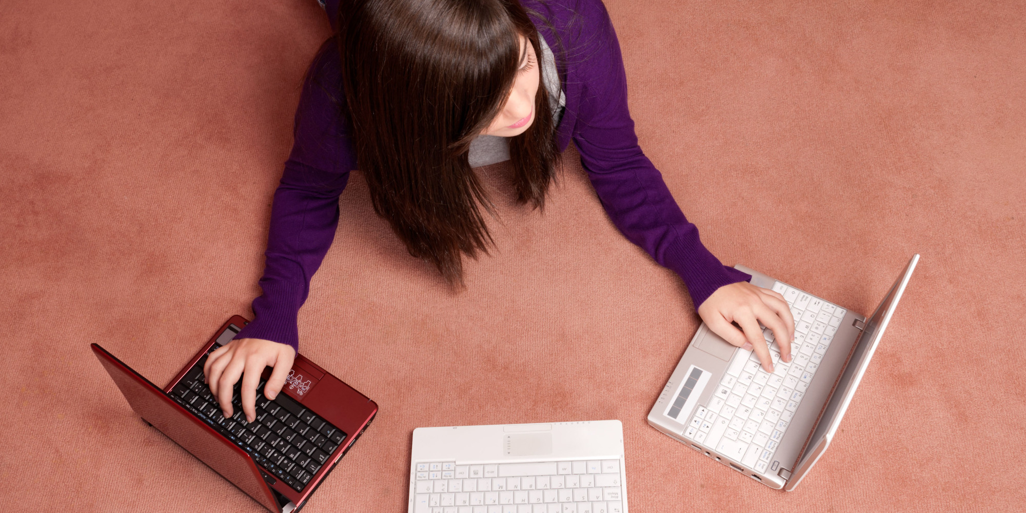 CYXHJP Young woman multitasking with three laptop lying on floor